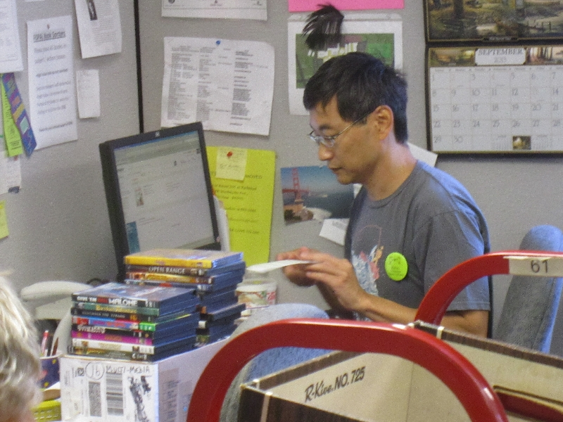 Dean researching DVDs online before pricing for sale